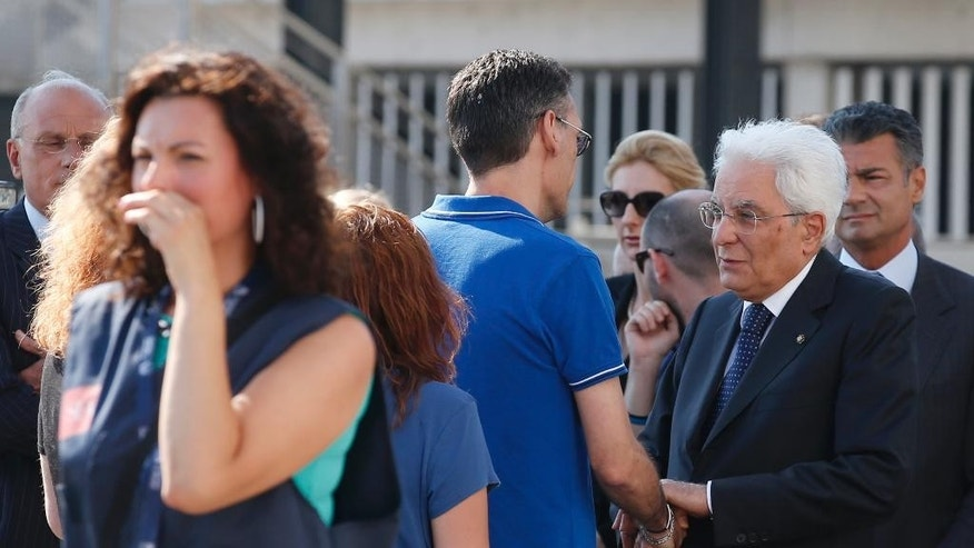 Relatives of four Italian victims of last week's truck attack in Nice, surround Italian President Sergio Mattarella, right, as they wait the coffins of their beloved one to arrive at the Malpensa airport near Milan, Italy, Wednesday, July 20, 2016. A large truck mowed through revelers gathered for Bastille Day fireworks in Nice, killing more than 80 people as it bore down for more than a mile along the Riviera city's famed waterfront promenade. (AP Photo/Antonio Calanni)