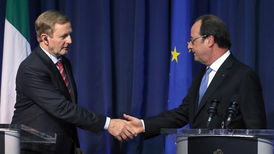 French President Francois Hollande, right, and Ireland's Taoiseach (Prime Minister) Enda Kenny shake hands during a press conference at Government Buildings in Dublin, Thursday July 21, 2016. (Niall Carson /PA via AP)