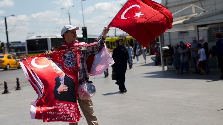 "A street vendor sells flags, some showing Turkish President Recep Tayyip Erdogan in central Istanbul, Thursday, July 21, 2016. President Erdogan on Wednesday declared a three-month state of emergency following a botched coup attempt, declaring he would rid the military of the ""virus"" of subversion and giving the government sweeping powers to expand a crackdown that has already included mass arrests and the closure of hundreds of schools. (AP Photo/Petros Giannakouris)"