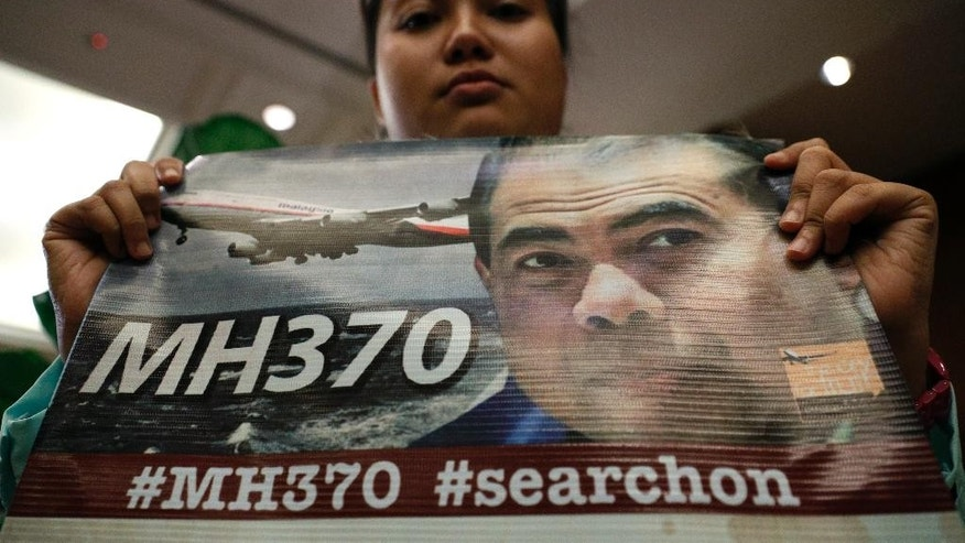 A family member of a passenger on board the Malaysia Airlines Flight 370 that went missing March 8, 2014 holds up a placard during a special press conference in Kuala Lumpur, Malaysia, Thursday, July 21, 2016.  The oceanographer whose calculations helped an American adventurer find potential debris from Flight 370 said Thursday that the Malaysia Airlines jetliner could have crashed slightly north of the current search area. (AP Photo/Vincent Thian)
