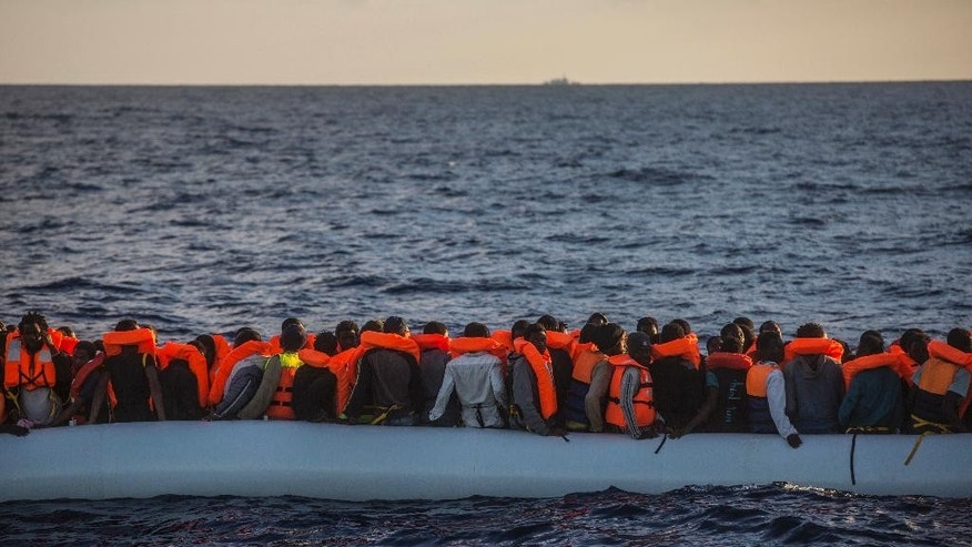 In this early Tuesday, July 19, 2016 photo, sub-Saharan refugees and migrants on an overcrowded dinghy wait to be rescued by a team of the Spanish NGO Proactiva Open Arms, in the Mediterranean Sea, 38 kilometers (24 miles) north of Sabratha, Libya, inside the so called Search and Rescue zone SAR. (AP Photo/Santi Palacios)