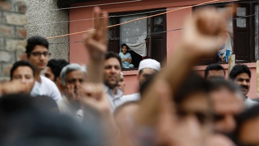 A young Kashmiri girl watches from the window of her home, as protestors shout freedom slogans on a street in Srinagar, Indian controlled Kashmir, Friday, July 22, 2016. The largest street protests in recent years in the disputed region, that left dozens of people dead and hundreds injured, erupted more than a week ago after Indian troops killed a popular young rebel leader. (AP Photo/Mukhtar Khan)