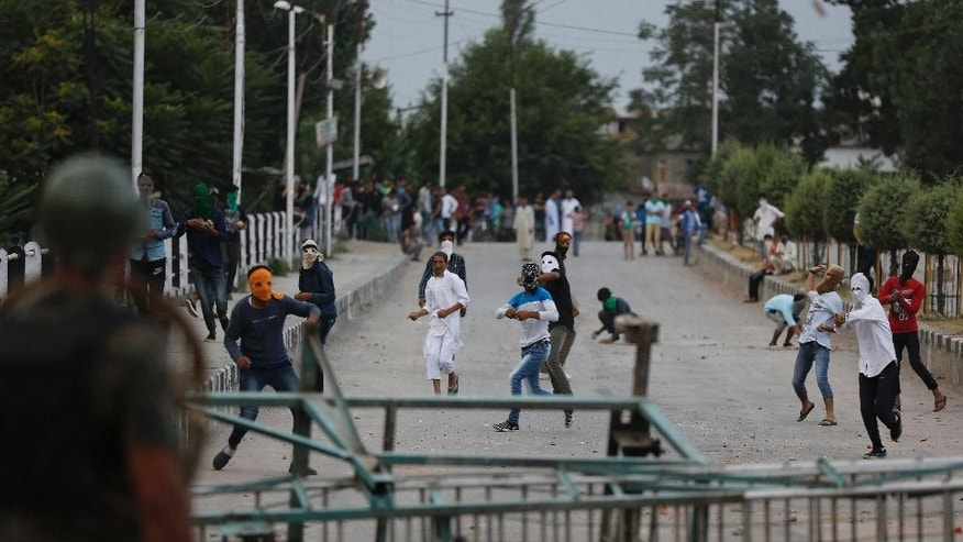 Kashmiri protesters throw stones at Indian paramilitary soldiers and policemen in Srinagar, Indian controlled Kashmir, Friday, July 22, 2016. The largest street protests in recent years in the disputed region, that left dozens of people dead and hundreds injured, erupted more than a week ago after Indian troops killed a popular young rebel leader. (AP Photo/Mukhtar Khan)