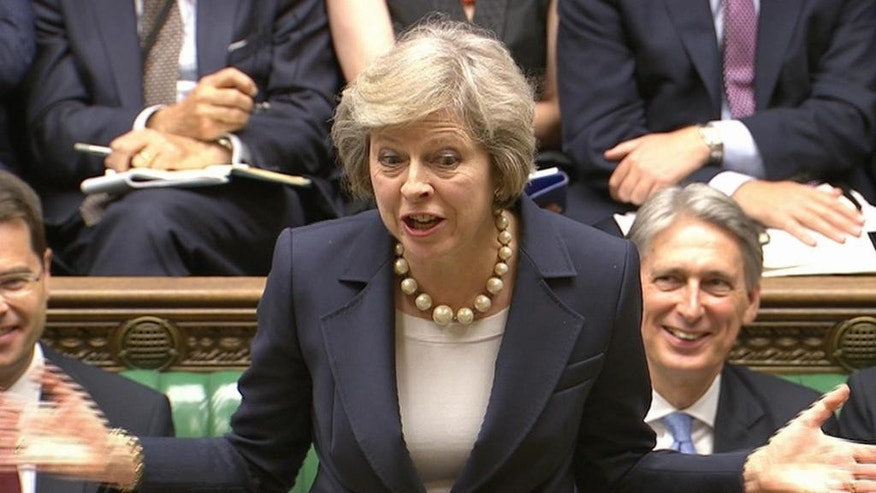In this grab taken from video British Prime Minister Theresa May speaks during her first session of Prime Minister's Questions at the House of Commons, in London, Wednesday July 20, 2016. Chancellor of the Exchequer Philip Hammond sits at right. Prime Minister Theresa May is making her first overseas trip as Britain's leader on Wednesday to meet German Chancellor Angela Merkel, a key figure in negotiating Britain's exit from the European Union. (Parliamentary Recording Unit via Associated Press Video) TV OUT - NO ARCHIVE