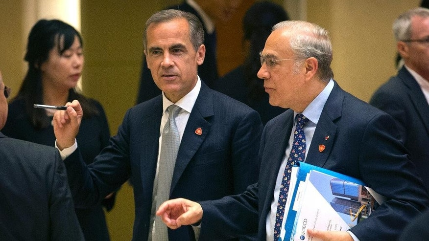 Mark Carney, Governor of the Bank of England and Chairman of the G20 Financial Stability Board, left, and Angel Gurria, Secretary-General for the Organization for Economic Cooperation and Development (OECD), right, arrive for a press conference for the 1+6 Roundtable on promoting economic growth at the Diaoyutai State Guesthouse in Beijing, Friday, July 22, 2016. The head of the International Monetary Fund called Friday to end uncertainty over Britain's vote to leave the European Union she says is dampening global economic growth. (AP Photo/Mark Schiefelbein)