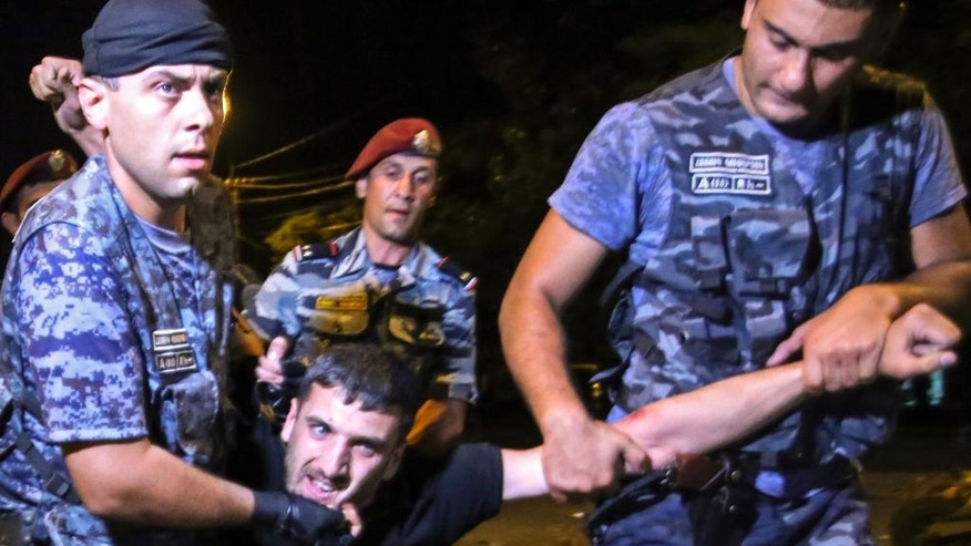 Police detain a protester while clearing out the protest camp in Yerevan, Armenia, Thursday, July 21, 2016. More than 50 people have been injured in clashes near a police station in Armenia's capital where armed men have been holding hostages for four days and protesters erected barricades on a nearby avenue. (Aram Kirakosyan/PAN Photo via AP)