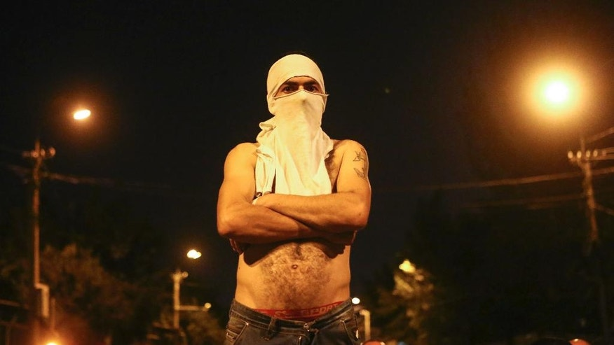 A protester stands on a barricade confronting a police cordon near a police station in Yerevan, Armenia, Thursday, July 21, 2016. More than 50 people have been injured in clashes near a police station in Armenia's capital where armed men have been holding hostages for four days and protesters erected barricades on a nearby avenue. (Hrant Khachatryan/PAN Photo via AP)