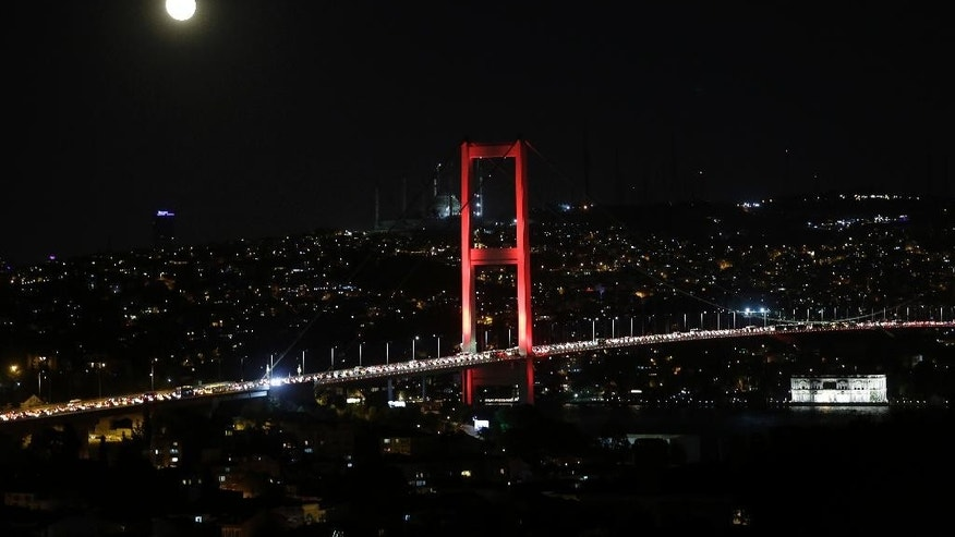 The moon rises behind Bosporus Bridge as pro-goverment supporters gather on the bridge to protest, late Thursday, July 21, 2016. Turkish lawmakers approved a three-month state of emergency, endorsing new powers for Turkey's President Recep Tayyip Erdogan that would allow him to expand a crackdown that has already included mass arrests and the closure of hundreds of schools, in the wake of the July 15 failed coup. (AP Photo/Petros Giannakouris)