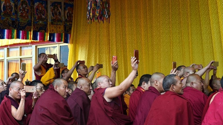In this Thursday, July 21, 2016 photo released by Xinhua News Agency, Tibetan monks take smartphones pictures during the Kalachakra ritual in Xigaze, southwest China's Tibet Autonomous Region. Tibetan groups say Chinese officials have begun dismantling buildings at Larung Gar, one of the world's largest centers of Tibetan Buddhist learning. (Chogo/Xinhua via AP)