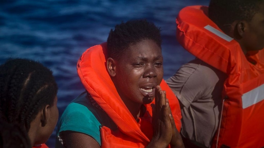 A Nigerian woman reacts onboard a boat of the Spanish NGO Proactiva Open Arms during a rescue operation on the Mediterranean sea, 19 miles north of Az Zawiyah, Lybia, on Thursday, July 21, 2016. Over the past weeks, vessels from NGOs, several nations' military fleets and passing cargo ships have all rescued migrants from unseaworthy boats launched from Libya's shores. (AP Photo/Santi Palacios)