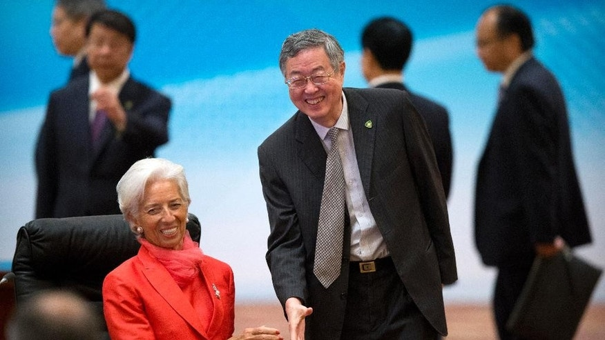 International Monetary Fund (IMF) director Christine Lagarde, left, is greeted by Zhou Xiaochuan, governor of the People's Bank of China, right, at the 1+6 Roundtable on promoting growth in the Chinese and global economies at the Diaoyutai State Guesthouse in Beijing, China, Friday, July 22, 2016. (AP Photo/Mark Schiefelbein)