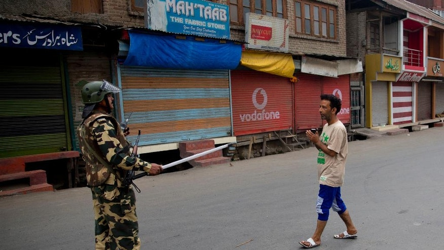 An Indian Paramilitary soldier stops a Kashmiri Muslim man in Srinagar, Indian controlled Kashmir, Friday, July 22, 2016. Restrictions and security lockdowns are nothing new for Kashmiris. The region witnessed months of clampdown during massive public uprisings against Indian rule in 2008 and 2010. Frequent separatist calls for shutdown and protests too are routinely met with security lockdowns. (AP Photo/Dar Yasin)