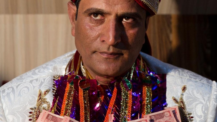 In this Thursday, July 21, 2016 photo, Kashmiri groom Shiekh Naseer Ahmed during his wedding ceremony in Srinagar, Indian controlled Kashmir. Ahmed's marriage date was fixed months back, with elaborate celebration plans, yet his home looks like anyone else's. There are no floral or light decorations, no hustle and bustle. Only close relatives are invited to the modest meal that is being prepared. His unusually humble nuptials reflect how ordinary life is muted in Srinagar, the urban heart of Indian-controlled Kashmir, as authorities attempt to quash protests against Indian rule.(AP Photo/Dar Yasin)