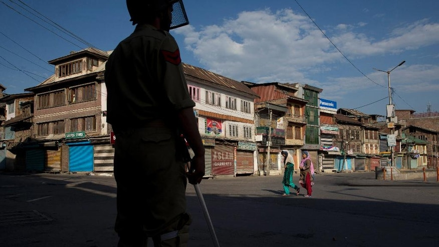 In this Thursday, July 21, 2016 photo, Kashmiri women walk on a deserted street, past an Indian policeman during curfew in Srinagar, Indian controlled Kashmir. Like much of the rest of Kashmir, the sprawling, densely populated neighborhoods have been under curfew since July 9, a day after Indian government forces killed a popular leader of the region's largest rebel group. Yet public defiance has persisted, sparking deadly clashes between Kashmiris and Indian government forces that left dozens dead and hundreds injured. Separatist leaders have called general strikes. (AP Photo/Dar Yasin)