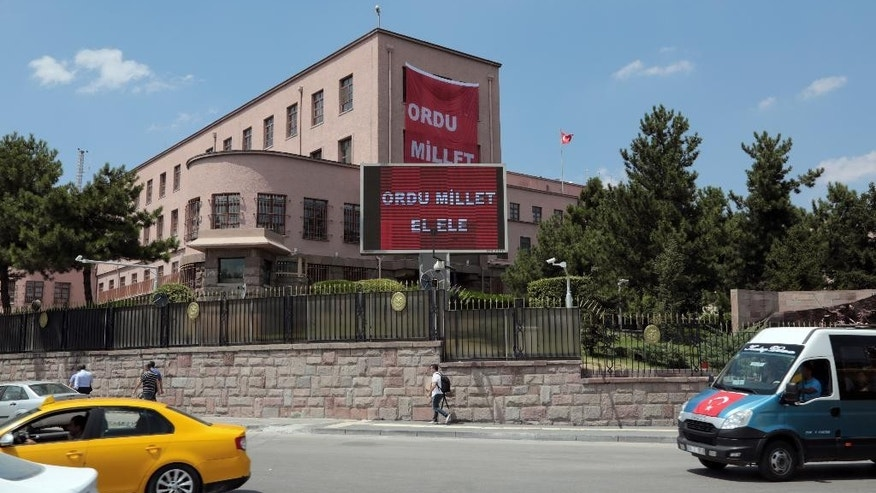 "A huge banner hang in front of the headquarters of Turkish military that reads ""The army and the nation hand in hand"" in Ankara, Turkey, Friday July 22, 2016. Some Muslim faithful in Ankara welcomed Friday a declaration of a state of emergency by the top authorities, a move that gives President Recep Tayyip Erdogan sweeping powers in ruling the country. (AP Photo/Burhan Ozbilici)"