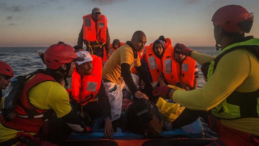 Refugees and migrants overcrowd a wood boat as they are rescued by a team of the Spanish NGO Proactiva Open Arms during a rescue operation on the Mediterranean sea, about 19 miles north of Az Zawiyah, Libya, on Thursday, July 21, 2016. Over the past weeks, vessels from NGOs, several nations' military fleets and passing cargo ships have all rescued migrants from unseaworthy boats launched from Libya's shores. (AP Photo/Santi Palacios)