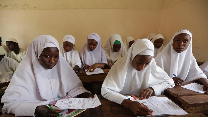 In this photo taken Wednesday April. 6, 2016 Muslim girls take exams in a school in Kano, Nigeria. Nigerian girls have the right to wear the hijab headscarf to school, an appeals court has ruled in a country where suicide bombers have abused Islamic dress to hide their deadly weapons. (AP Photo/Sunday Alamba)