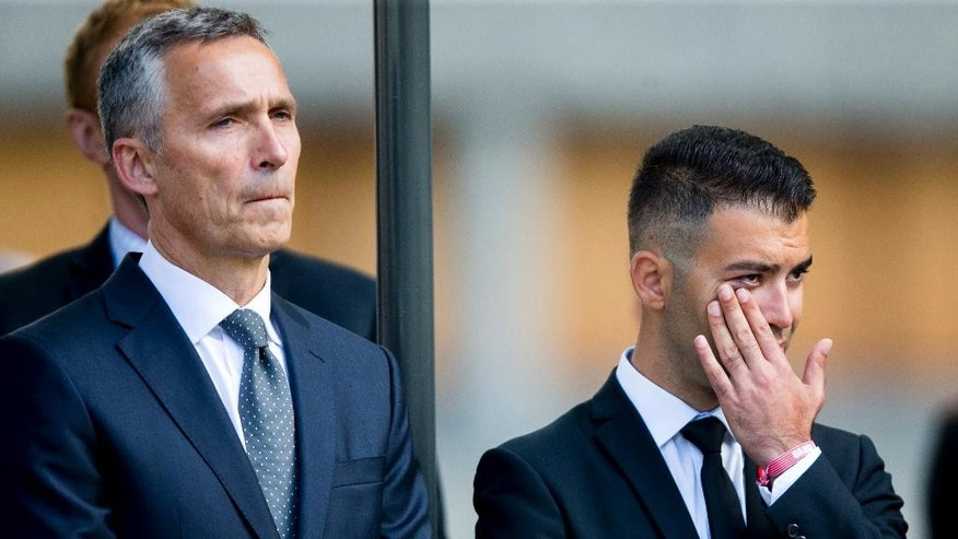 Jens Stoltenberg, NATO Secretary-General and Norway's former prime minister during the attacks in 2011, and President of Norwegian Labour party youth division Mani Hussaini, right, attends a wreath laying ceremony in the government quarter in Oslo, Norway, Friday July 22, 2016. Norway is paying homage to the 77 people killed in a bombing and shooting rampage five years ago, with church services and events to mark one of the darkest days in the Scandinavian country's history. (Vegard Wivestad Groett/NTB via AP)