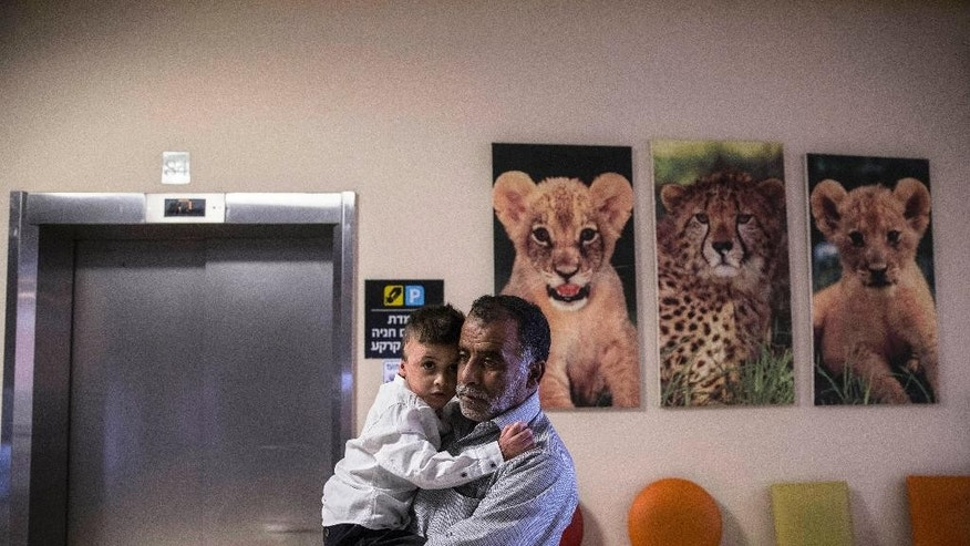 A Palestinian relative carries Ahmad Dawabsheh, the sole survivor of a West Bank arson attack, at the Tel HaShomer Hospital in the city of Ramat Gan, Israel, Friday, July 22, 2016. The Palestinian boy who was seriously wounded in a firebomb attack that killed the rest of his family a year ago has been released from hospital. (AP Photo/Tsafrir Abayov)