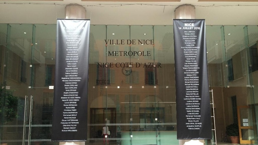 The names of the victims of truck attack in Nice, that killed 84 people last Thursday hang from two pillars at Nice City Hall in Nice, France Friday July 22, 2016. (AP Photo/Maeva Bambuck)