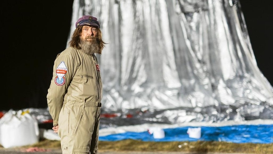In this Monday, July 11, 2016 photo released Wednesday, July 20, 2016 by Morton, Russian adventurer Fedor Konyukhov stands by his helium and hot-air balloon being inflated before liftoff on his record attempt to fly solo in a balloon around the world nonstop in Northam in Western Australia state. Konyukhov, 65, now flying at more than 6,000 meters (20 feet) above the ground, was battling sleep deprivation, freezing temperatures and ice in his oxygen mask as he nears the end of his record attempt to fly solo around the world nonstop, his son said on Wednesday, July 20, 2016. (Oscar Konyukhov/Morton via AP)