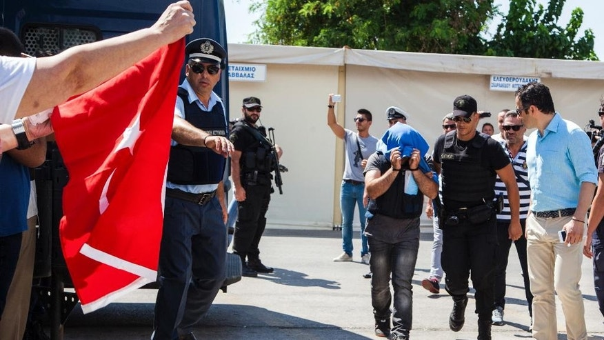 A Turkish military officer is transferred to a court hall in the city of Alexandroupolis, northern Greece, Thursday, July 21, 2016. Eight Turkish military personnel who fled to Greece a board a helicopter during an attempted coup in their country are testifying in court during their trial on charges of entering Greece illegally. Turkey is seeking their return to stand trial for participation in Friday's coup attempt. The eight deny any involvement and have applied for asylum, saying they fear for their lives if returned. (Antonis Pasvantis/InTime News via AP)
