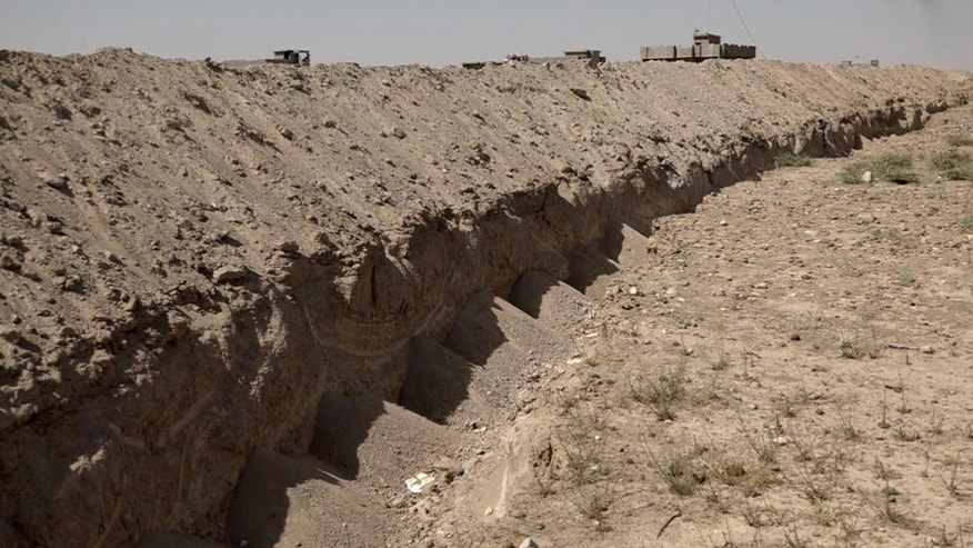 This image made from video on Friday, July 22, 2016 shows a freshly-dug trench on the outskirts of Fallujah, Iraq. Iraq's army is turning to a radical, almost medieval method to control Fallujah after recapturing it from the Islamic State group last month: It is digging a trench that will almost entirely encircle the city, aimed at preventing it from falling back into the hands of militants. (AP photo via AP video)