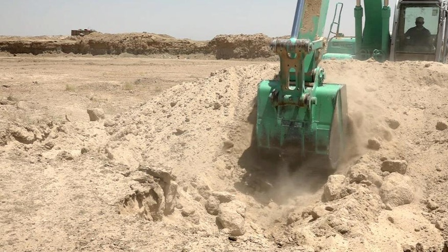 In this image made from video on Friday, July 22, 2016, a worker digs a trench on the outskirts of Fallujah, Iraq. Iraq's army is turning to a radical, almost medieval method to control Fallujah after recapturing it from the Islamic State group last month: It is digging a trench that will almost entirely encircle the city, aimed at preventing it from falling back into the hands of militants. (AP photo via AP video)