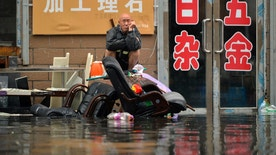 In this Thursday, July 21, 2016 photo, a man sits outside of a flooded shop in Shenyang in northeastern China's Liaoning Province. Dozens of people have been killed and dozens more are missing across China after a round of torrential rains swept through the country earlier this week, flooding streams, triggering landslides and destroying houses. (Chinatopix via AP)