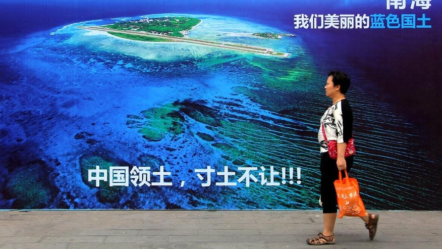"""FILE - In this July 14, 2016 file photo, a woman walks past a billboard featuring an image of an island in South China Sea on display with Chinese words that read: """"South China Sea, our beautiful motherland, we won't let go an inch"""" in Weifang in east China's Shandong province. An international arbitration panel's decision on the contested waters of the South China Sea so far is fueling regional tensions rather than tamping them down. In the ensuing 11 days, China has responded to the sweeping victory for the Philippines by flexing its military might. The Philippines faces pressure both at home and abroad not to cede an inch to China after the July 12 decision by a tribunal at The Hague-based Permanent Court of Arbitration. (Chinatopix via AP, File)"""