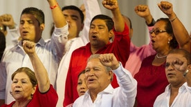 """FILE - In this June 1, 2014 file photo, El Salvador's President Salvador Sanchez Ceren sings the Farabundo Marti National Liberation Front anthem during a rally with party supporters after his swearing-in ceremony in San Salvador, El Salvador. Sanchez Ceren says he has begun talks with political parties on a new """"national reconciliation"""" law after the Supreme Court overturned an amnesty covering crimes committed during the 1980-1992 civil war. (AP Photo/Moises Castillo, File)"""