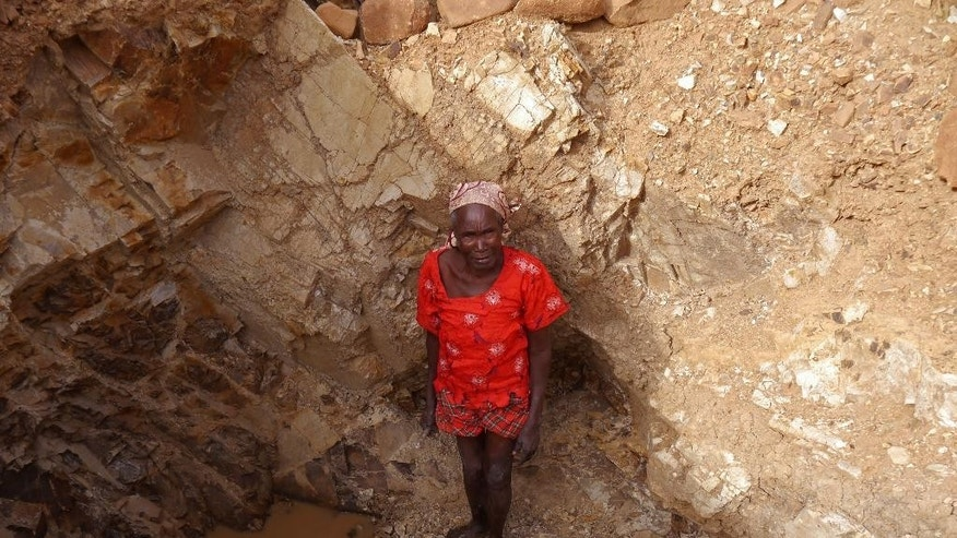 In this photo taken on Thursday, June 16, 2016, an old woman stand inside a quarry were she works with others crushing rocks in Maroua, Cameroon. In a northern Cameroon town menaced by food insecurity and suicide bombers, women as old as 85 are spending long, grueling days crushing rocks into gravel to earn a living. The dangerous, sometimes fatal work often pays no more than $2 per day. (AP Photo/Joel Kouam)