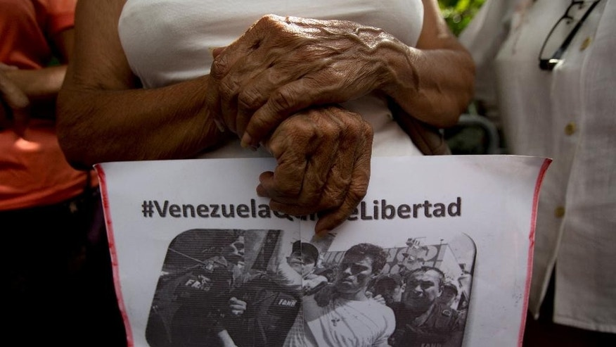 "A supporter of jailed opposition leader Leopoldo Lopez holds a leaflet with an image of Lopez and a hashtag that reads in Spanish; ""Venezuela Wants Freedom"" outside a court house where an appeal hearing for Lopez is scheduled, in Caracas, Venezuela, Friday, July 22, 2016. In 2015, Lopez was sentenced to nearly 14 years in jail for inciting violence at anti-government protests. (AP Photo/Fernando Llano)"