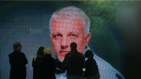 A portrait is displayed as colleagues and people gather at the coffin of Pavel Sheremet to pay their respects at his memorial ceremony in Kiev, Ukraine, Friday, July 22, 2016. Hundreds of local residents and journalists have come to pay their respects to a prominent journalist who died in a car bombing in the Ukrainian capital of Kiev earlier this week. (AP Photo/Efrem Lukatsky)