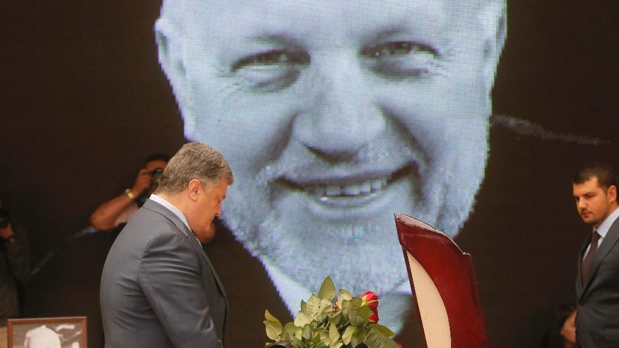 A portrait of Pavel Sheremet is displayed as Ukrainian President Petro Poroshenko stands  at the coffin of killed journalist Pavel Sheremet at a memorial ceremony in Kiev, Ukraine, Friday, July 22, 2016. Hundreds of local residents and journalists have come to pay their respects to a prominent journalist who died in a car bombing in the Ukrainian capital of Kiev earlier this week. (AP Photo/Efrem Lukatsky)