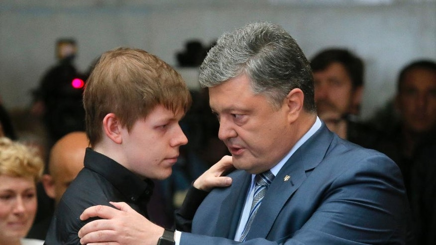Ukrainian President Petro Poroshenko, right, talks to Pavel Sheremet's son Nikolay at Sheremet's memorial ceremony in Kiev, Ukraine, Friday, July 22, 2016. Hundreds of local residents and journalists have come to pay their respects to a prominent journalist who died in a car bombing in the Ukrainian capital of Kiev earlier this week. (AP Photo/Efrem Lukatsky)