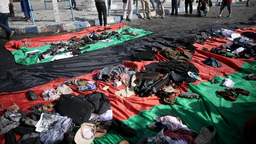 CAPTION CORRECTION: CORRECTS NAME OF PHOTOGRAPHER TO MASSOUD HOSSAINI -- Afghans look at property left behind by victims of an explosion that struck a protest march, that is displayed on a large representation of the Afghan flag, in Kabul, Afghanistan, Saturday, July 23, 2016. Witnesses in Kabul say that an explosion causing multiple casualties struck the march by members of Afghanistan's largely Shiite Hazara ethnic minority group, who were demanding that a major regional electric power line be routed through their impoverished home province. (AP Photo/Massoud Hossaini)
