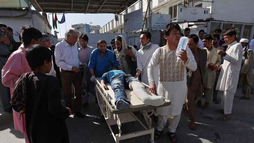 Afghans help an injured man at a hospital after an explosion struck a protest march, in Kabul, Afghanistan, Saturday, July 23, 2016. Witnesses in Kabul say that an explosion struck the protest march by members of Afghanistan's largely Shiite Hazara ethnic minority group, demanding that a major regional electric power line be routed through their impoverished home province. (AP Photo/Rahmat Gul)