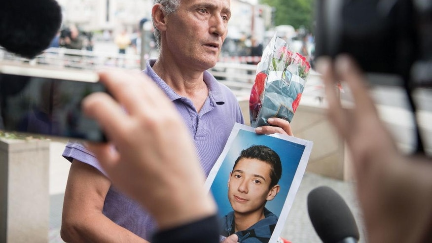The father of a victim shows a picture of his son near the Olympia shopping center where a shooting took place leaving nine people dead the day before on Saturday, July 23, 2016 in Munich, Germany. (AP Photo/Sebatian Widmann)