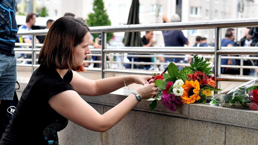 A woman puts down flowers near a mall where a shooting took place leaving nine people dead the day before on Saturday, July 23, 2016 in Munich, Germany. (AP Photo/Kerstin Joensson)