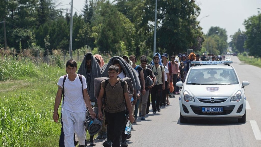 Migrants and refugees walk down a road escorted by a police vehicle in Indjija, some 40 kilometers (24 miles) northwest of Belgrade, Serbia, Saturday, July 23, 2016. Hundreds of migrants and asylum seekers set off on foot Friday toward Serbia's border with Hungary to protest its decision to keep its border closed for most people trying to reach the European Union. (AP Photo/Marko Drobnjakovic)