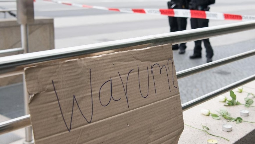 "A sign reading ""why"" is fixed where a shooting took place in front of a fast food restaurant leaving nine people dead the day before on Saturday, July 23, 2016 in Munich, Germany. (AP Photo/Sebastian Widmann)"