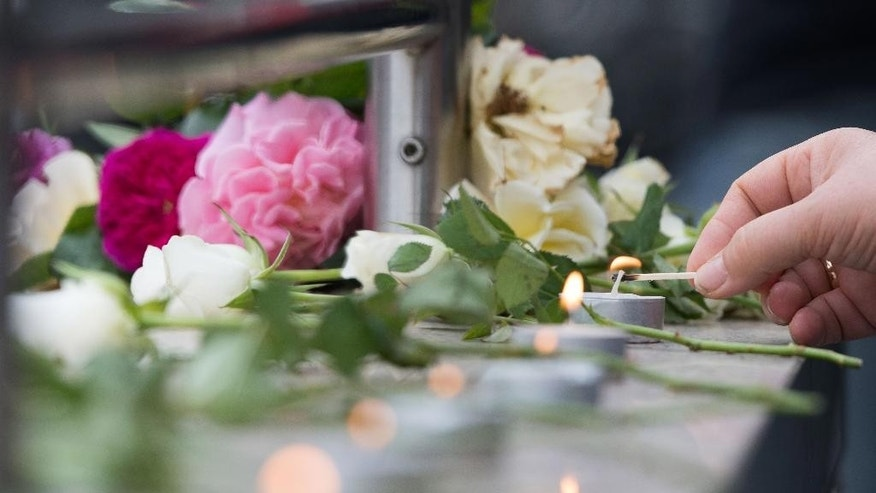 Candles are lit near a mall where a shooting took place leaving nine people dead the day before on Saturday, July 23, 2016 in Munich, Germany. (AP Photo/Sebastian Widmann)