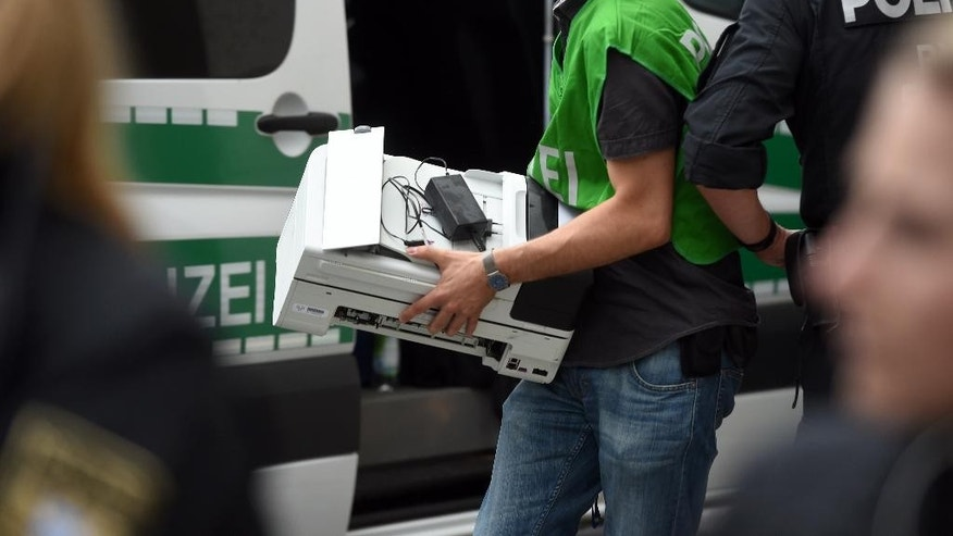 Police officers secure evidence from a flat in Dachauer Strasse after a shooting the day before leaving nine people dead on Saturday, July 23, 2016 in Munich, Germany. (Tobias Hase/dpa via AP)