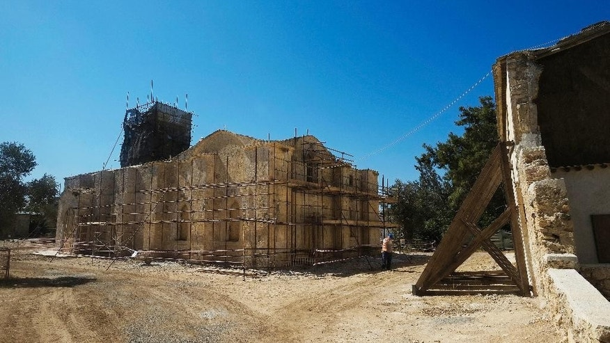 In this photo taken on Monday July 18, 2016, a Turkish Cypriot worker works at the Agios Panteleimonas monastery, which is under restoration in Myrtou in the Turkish Cypriot northern part of the Mediterranean island of Cyprus. . The first phase of work, supported by 725,000 euros ($800,000) in EU funds, seeks to reinforce sandstone walls in a compound that includes a church, monks' residences and guesthouses. (AP Photo/Petros Karadjias)