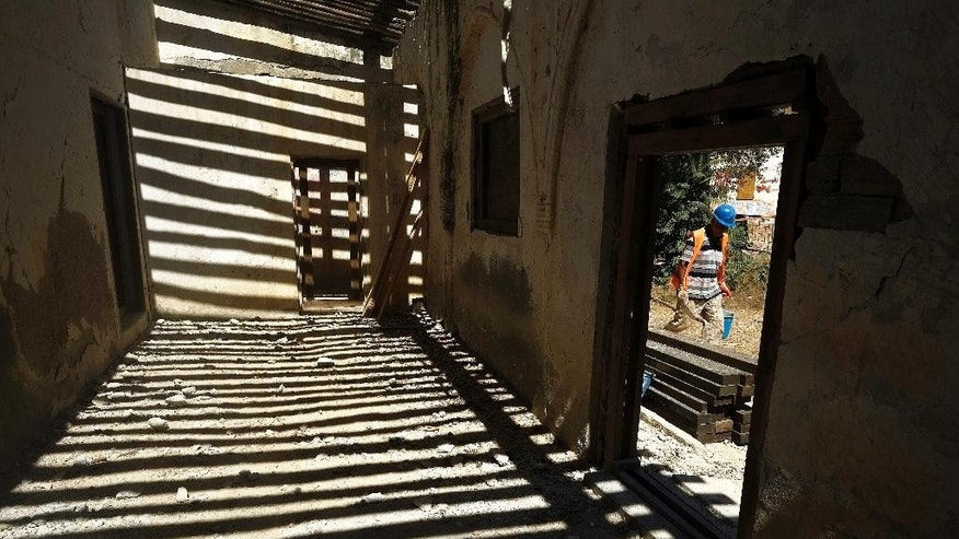 In this photo taken on Monday July 18, 2016, a Turkish Cypriot worker walks, at the Agios Panteleimonas monastery, which is under restoration in Myrtou in the Turkish Cypriot northern part of the Mediterranean island of Cyprus. The first phase of work, supported by 725,000 euros ($800,000) in EU funds, seeks to reinforce sandstone walls in a compound that includes a church, monks' residences and guesthouses. Onkal said he hopes to use original timbers, sandstone blocks and mud bricks to restore the monastery to its pre-partition splendor. (AP Photo/Petros Karadjias)