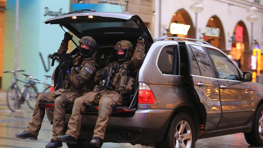 In this Friday, July 22, 2016 photo provided by Wael Ladki heavily armed police officers sit in the trunk of the SUV as they are on the hunt for possible fugitives after a shooting in a shopping mall in Munich, southern Germany. (Wael Ladki via AP)