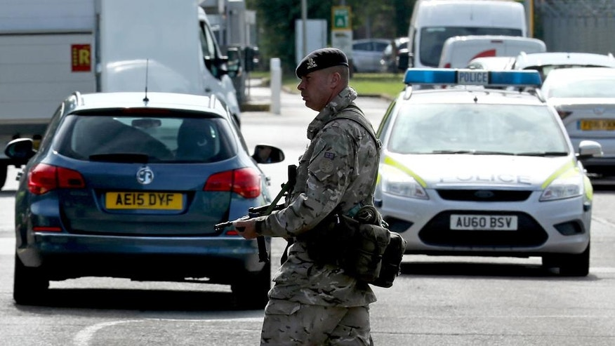 An armed guard patrols, at RAF Marham in Norfolk, after a serviceman was threatened with a knife near to the base, in Marham, England, Thursday July 21, 2016. UK authorities say they are searching for two people in the attempted abduction of a serviceman at a Royal Air Force base in eastern England. Police said Thursday that two men, one of whom had a knife, approached the serviceman while he was jogging. One of the men shouted at the serviceman and attempted to grab him, but the serviceman fought him off and got away. ( Chris Radburn/PA via AP)