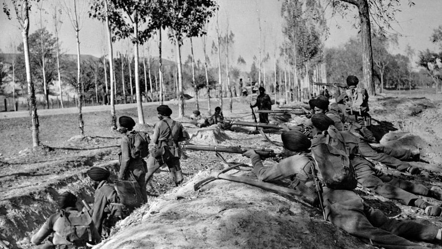 FILE- In this Nov. 9, 1947 file photo, Indian Sikh troops take up roadside positions on the Baramula Road to help force invaders further away from the Kashmir capital, Srinagar. A raid by armed tribesmen from north-western Pakistan forced Maharaja Hari Singh of the Himalayan kingdom of Jammu and Kashmir to seek help from India, which offered military assistance on the condition that the kingdom accede to India. The ruler accepted but insisted that the region would remain a largely autonomous state within the Indian union, with India managing its foreign affairs, defense, and telecommunication. The Indian military entered the region soon after, and the tribal raid spiraled into the first of two wars between India and Pakistan over Kashmir. The war ended in 1948 with a United Nations brokered ceasefire. (AP Photo/Max Desfor, File)