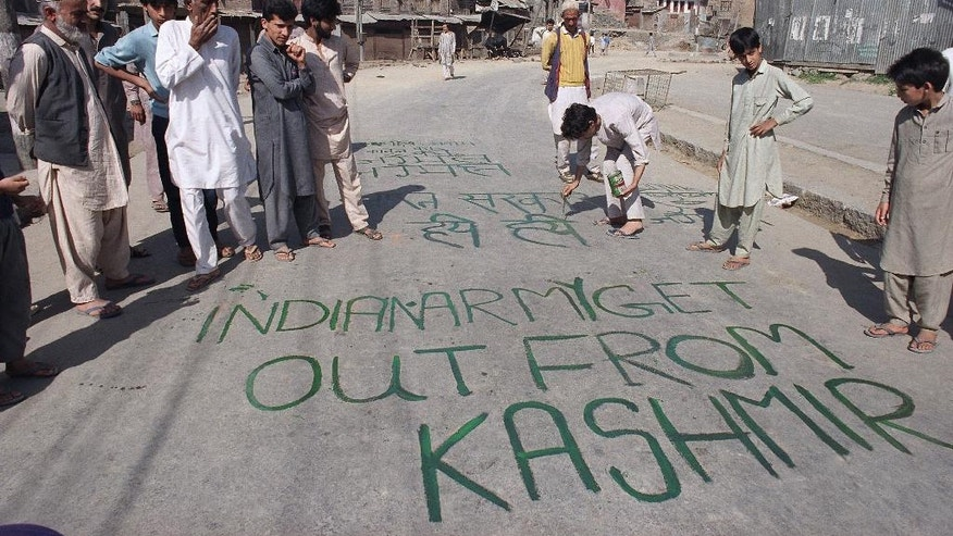 "FILE - In this May 25, 1990 file photo, a Kashmiri paints a graffiti that reads ""Indian Army Get Out From Kashmir"" on a street in the old city of Srinagar, India. By 1989 Kashmir was in the throes of a full blown anti-India rebellion. India poured in more troops into the already heavy militarized region to control the rebellion. Since 1989, more than 68,000 people have been killed in the uprising and the subsequent Indian military crackdown that has left ordinary Kashmiris traumatized. (AP Photo/Barbara Walton, File)"